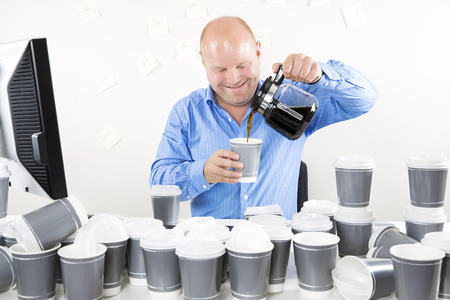 too much: Smiling businessman drinks too much coffee Stock Photo