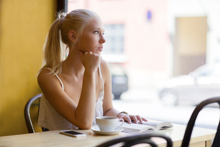 Pensive young woman at cafe looks out the window Stock Photo
