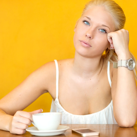 young woman sitting: Attractive blonde girl drinking coffee at cafe