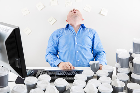 Overworked businessman drinks too much coffee