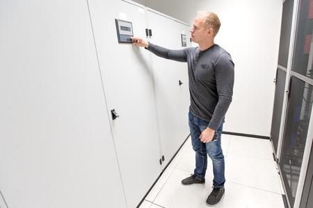 server side: IT engineer adjusts air conditioner in datacenter