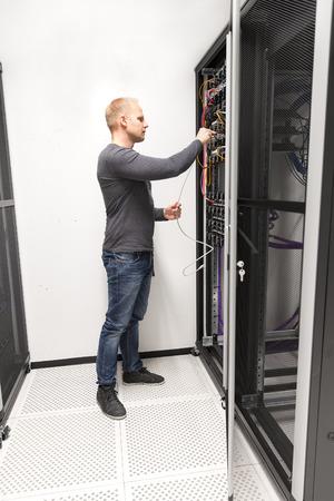 IT consultant installs network rack in datacenter photo