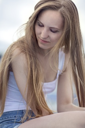 white singlet: Thinking young model woman sitting outdoor Stock Photo