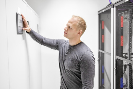 server side: Engineer adjusts air conditioner in datacenter