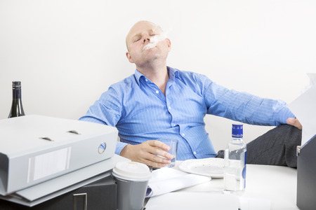 Businessman smokes and drinks at the office photo