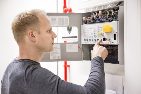 Technician checks fire panel in data center Stock Photo - 33033720