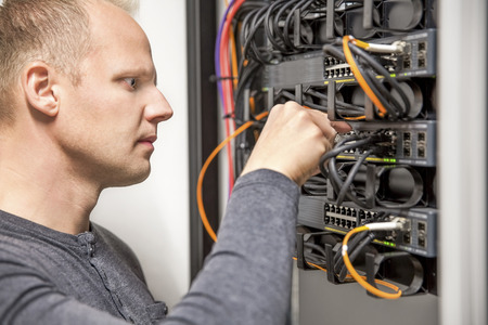 computer support: IT consultant connecting network cable into switch