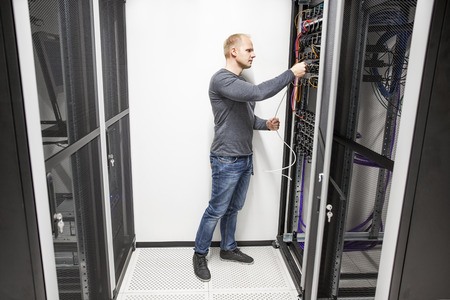 cabling: IT consultant works with network in datacenter