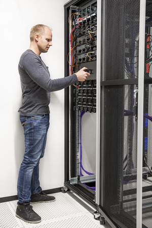 server side: IT engineer building network rack in datacenter