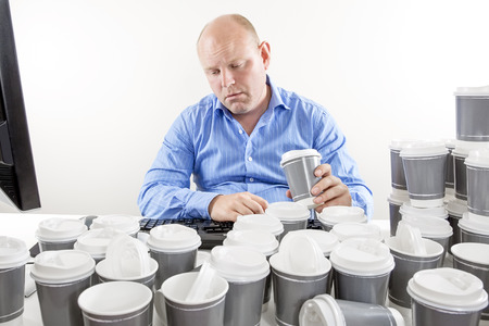 too much: Overworked businessman drinking too much coffee