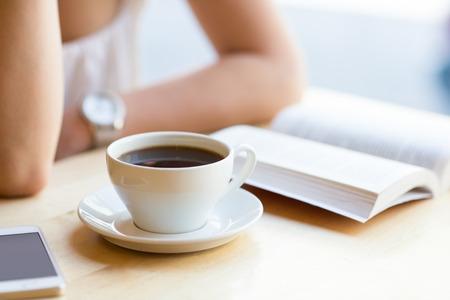 tazas de cafe: Mujer leyendo el libro y beber caf� en el caf�