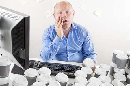 white collar worker: Overworked and exhausted businessman at the office Stock Photo