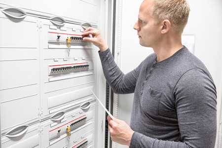 fuse: Technician works in large electric fuse cabinet