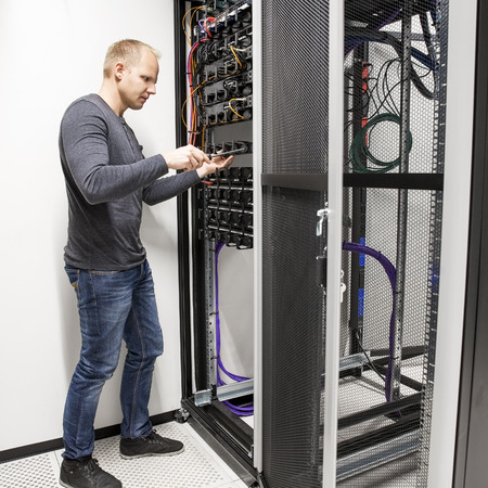 IT support: IT consultant building network rack in datacenter Stock Photo