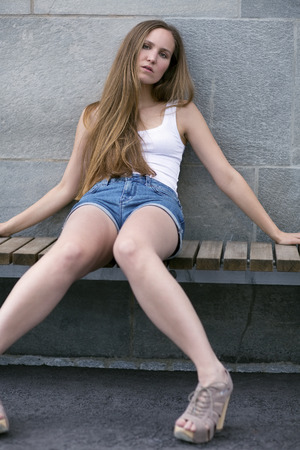 fine legs: Pretty young woman model on bench Stock Photo