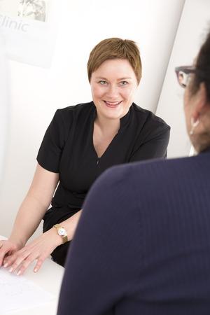 personas escuchando: Consulta al cliente en la cl�nica de tratamiento corporal Foto de archivo