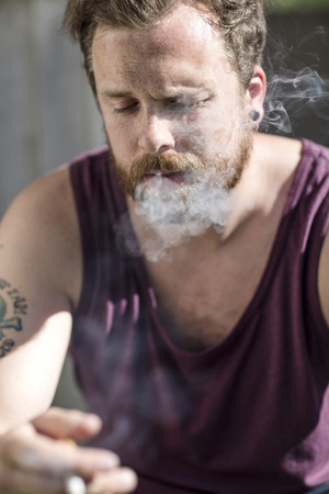 getting away from it all: Close up of man who smokes on the staircase Stock Photo