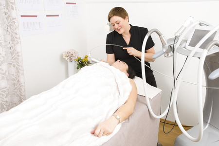 Woman undergoes face treatments at beauty clinic photo