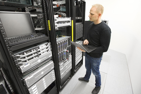 information technology: It consultant monitors servers in datacenter