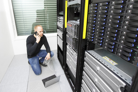 man working on computer: Problem solving IT consultant in datacenter