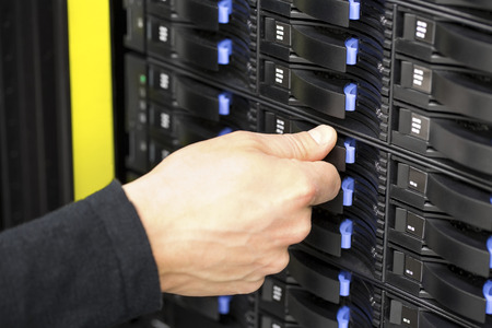data center data centre: IT consultant replaces SAN harddrive in datacenter Stock Photo