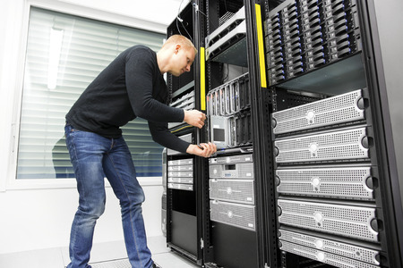 server side: IT engineer installs blade server in datacenter Stock Photo