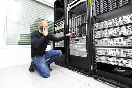 IT consultant calling support in datacenter Foto de archivo