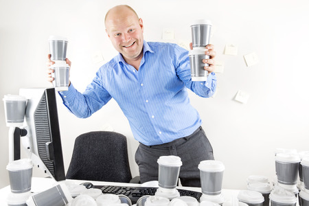 too: Happy businessman drinks too much coffee