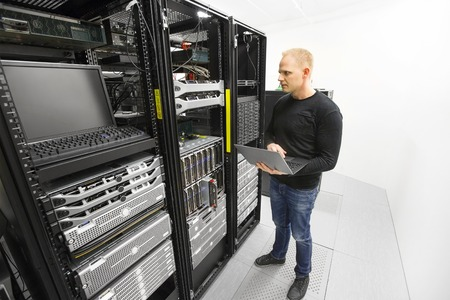It professional or technicial consultant monitors blade servers in data rack. Shot in datacenter. Standard-Bild