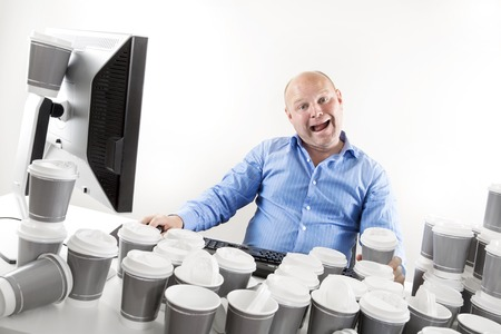 too much: Strange and funny looking office worker drinks too much coffee. Stock Photo