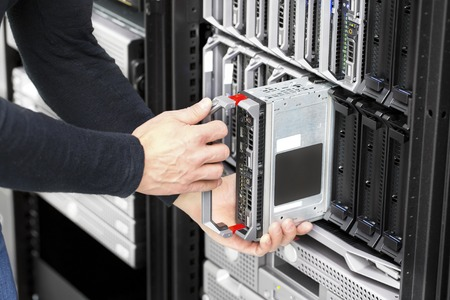 server side: It engineer or consultant working with installation of a blade server in data rack. Shot in a large datacenter.