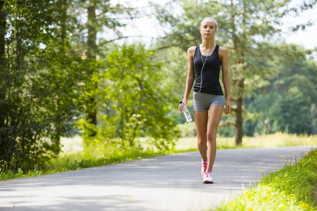 water park: Beautiful young and fit blonde woman walking on trail in the woods. Workout outdoor.