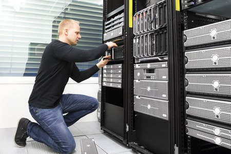 Close up of a IT engineer or technician who maintains storage area network SAN in a data rack. Shot in datacenter.