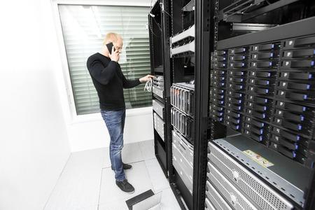 computer centre: Es ingeniero o t�cnico de monitores y de resoluci�n de problemas con los servidores y equipos de red en rack de datos. Herido de bala en el centro de datos. Foto de archivo