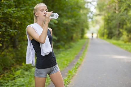 pantalones cortos: joven y bella mujer rubia en forma de tomar un descanso después de correr. De pie en el bosque y el agua potable. Foto de archivo
