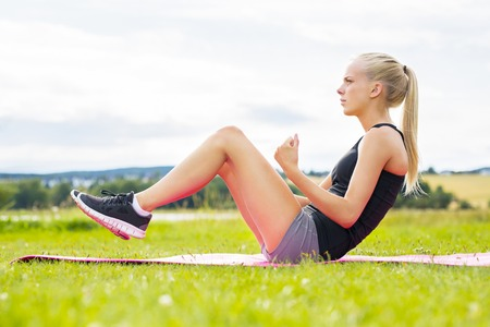cute teen: Beautiful woman doing sit ups on green grass in a park on workout mat. Stock Photo