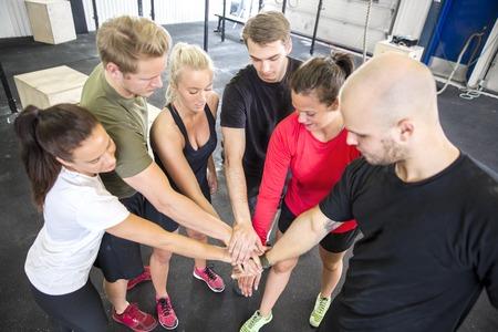 fitness hombres: Grupo de entrenamiento Motivado tomados de la mano en el centro de gimnasio de fitness. La motivación del equipo.