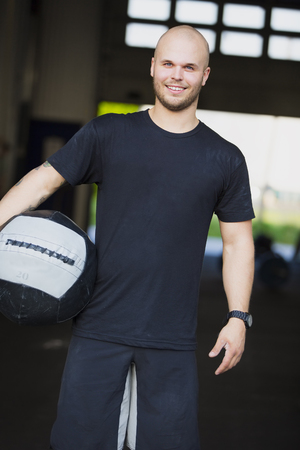 Smiling and well trained man with medicine ball at gym center.