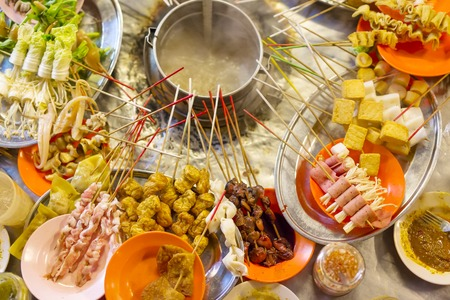 Traditional asian street food called lok lok. Sticks with meat, tofu, fish and vegetables ready to be boiled.