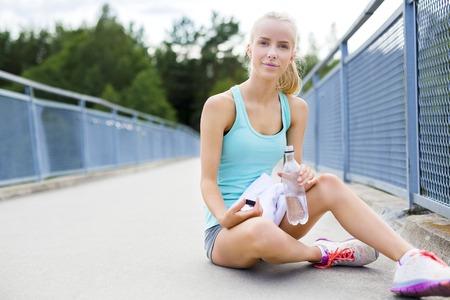 skinny: Corredora de atletismo sonriente joven descansa después de correr o trotar entrenamiento al aire libre. Bebe agua y se seca la cara con una toalla en un puente. Foto de archivo