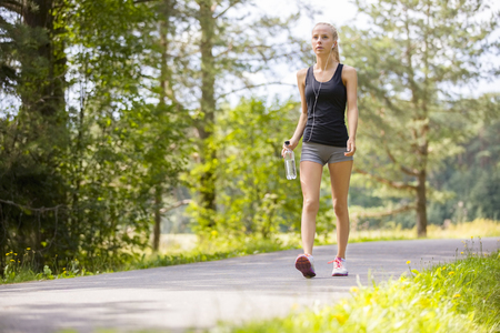 hacer footing: Hermosa mujer rubia joven y en forma camina sobre la pista en el bosque. Entrenamiento al aire libre.