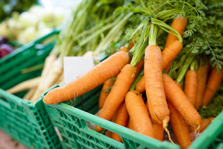 marchew: Organic carrots and other vegetables at farmers market. Healthy local food.