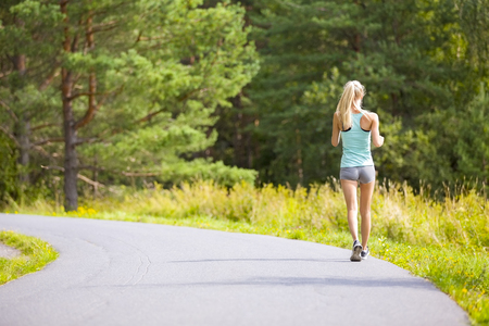 runs: Healthy and slim blonde woman runs or walks on a road in the forest. Workout outdoor a summer evening.