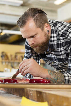 Close-up of a young adult craftsman who works with a guitar in a workshop for wood work and painting. Stock Photo