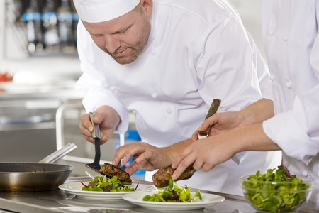 Smiling chef and his assistant prepare meat dish in a professional kitchen at restaurant or hotel.