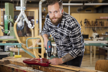 gitar: Young adult craftsman who works with a guitar in a workshop for wood work and painting. Using a drill to screw.