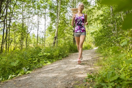 runs: Healthy and slim blonde woman runs or jogs on a trail in the forest. Workout outdoor. Stock Photo