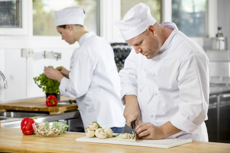 Professional chef chops up mushrooms and makes food in industrial kitchen. Archivio Fotografico