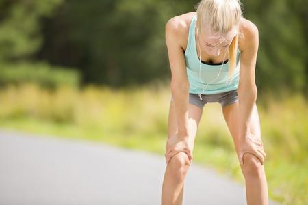 agotado: Atlético joven mujer corredor de descanso después de correr al aire libre en el bosque. La muchacha cansada que sostiene sus manos sobre las rodillas.