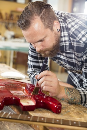 Close-up of a adult crafts man who works with a guitar in a workshop for wood work and painting.